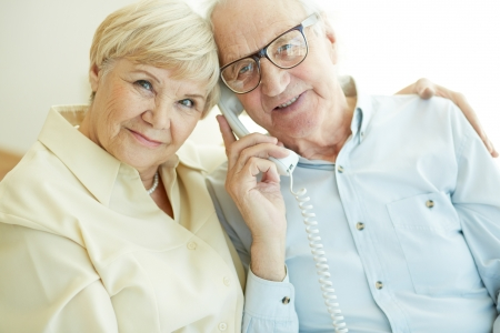 couple talking: Portrait of elderly woman looking at camera with her husband talking on the phone near by