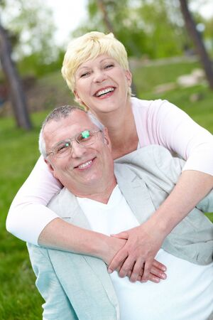 Happy mature couple laughing while having rest outside photo
