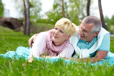 Happy mature couple lying on grass in the countryside photo