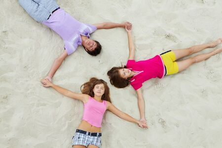 Above angle of calm teenage friends lying on sandy beach