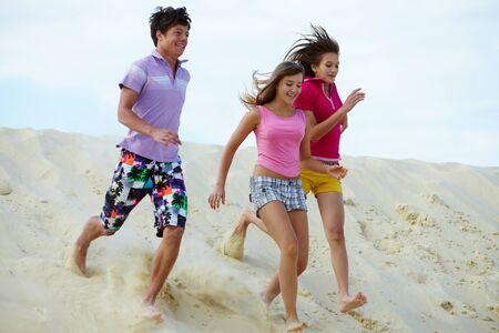 barefoot teens: Portrait of laughing teenage friends having fun on sandy beach