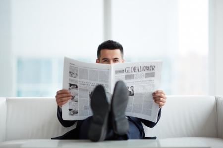 젊은 사업가 신문을 읽는 동안 카메라를보고 소파에