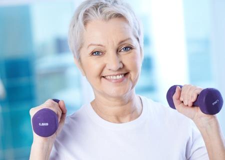 tercera edad: Retrato de la mujer mayor bastante ejercicio con pesas Foto de archivo