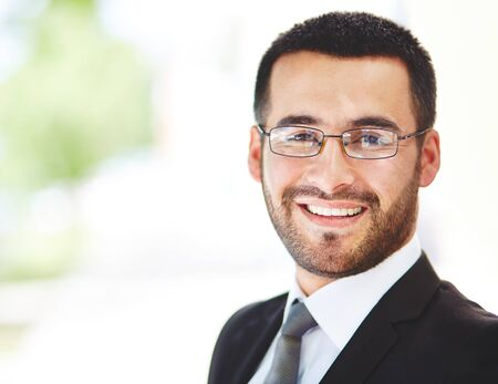formal portrait: Close-up portrait of a successful businessman looking at camera with smile