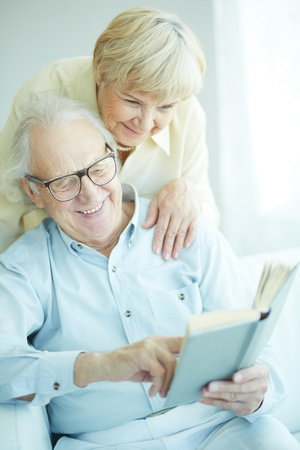 Portrait of a candid senior couple reading book together photo