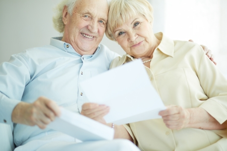 old papers: Portrait of a candid senior couple with paper looking at camera