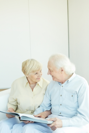 Portrait of a happy senior couple looking at one another while reading book photo
