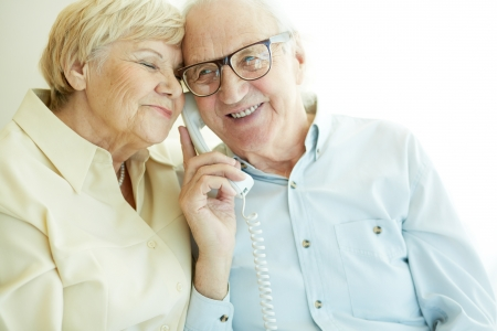 talking on telephone: Portrait of elderly man talking on the phone with his wife near by