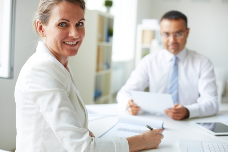 Happy mature businesswoman looking at camera with her colleague on background Stok Fotoğraf