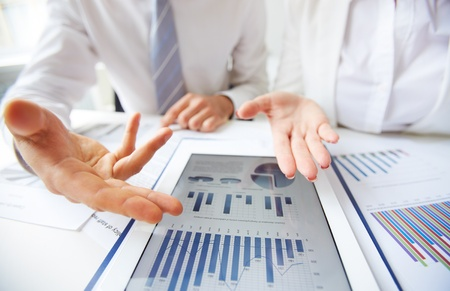 Close-up of female and male hands pointing at business document in touchpad photo