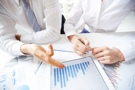 Close-up of female and male hands over business document in touchpad photo