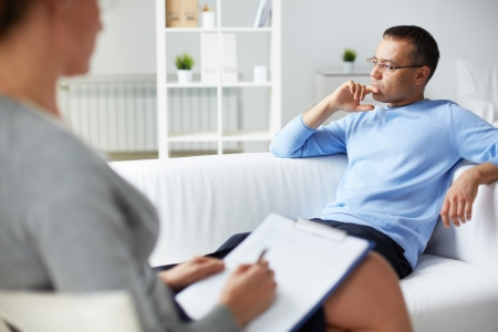 psicologia: Hombre pensativo tratando de relajarse en el sof� durante la sesi�n de terapia psicol�gica
