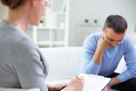 terapia psicologica: Mujer psicóloga consultora hombre pensativo durante la sesión de terapia psicológica Foto de archivo
