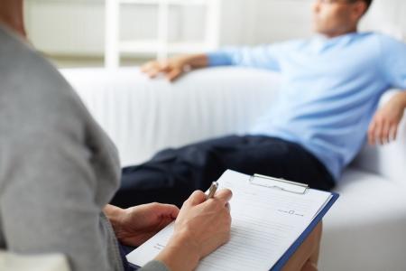 terapia psicologica: Psic�logo Mujer haciendo notas durante la sesi�n de terapia psicol�gica Foto de archivo