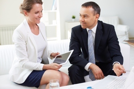 Mature businesswoman with touchpad looking at laptop while discussing plans with her boss in office photo