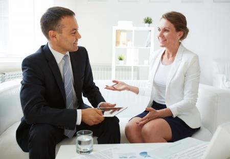 amigas conversando: Hombre de negocios maduro con touchpad mirando a su colega mientras se discuten nuevas ideas en la oficina