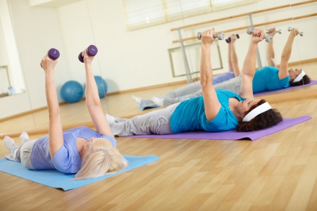Image of two mature females doing exercise with barbells in sport club photo