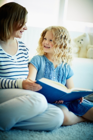 Portrait of cute girl listening to her mother reading an interesting story at home