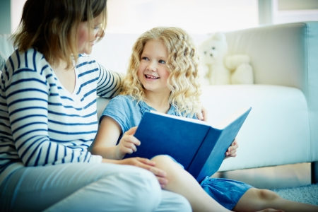 child reading: Portrait of cute girl looking at her mother while discussion of an interesting story at home Stock Photo