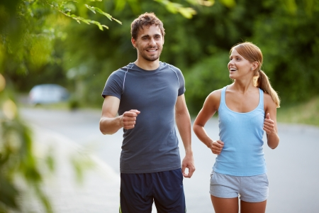 two friends talking: Photo of happy couple jogging on summer morning