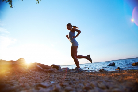 Photo of young woman running on the beach at sunrise Stock Photo