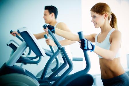 fitness hombres: Retrato de muchacha bonita en entrenamiento equipo deportivo especial en el gimnasio