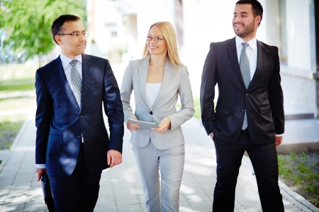 Image of friendly business team walking down street and talking photo
