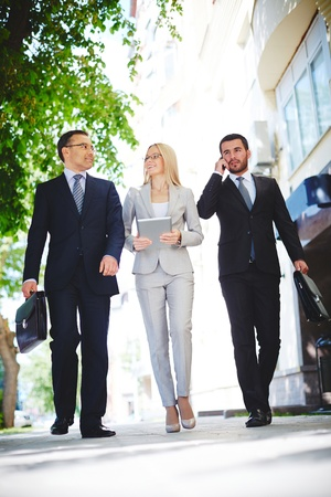 vertical: Mature businessman sharing experience with one of colleagues while going down urban street Stock Photo