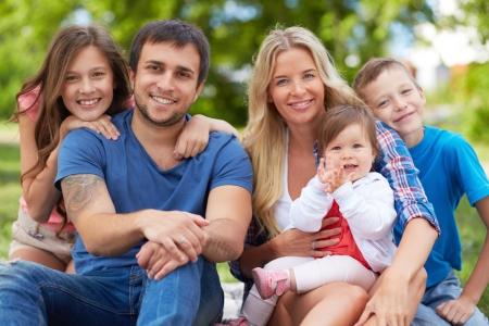 photo: Photo of happy family looking at camera outdoors
