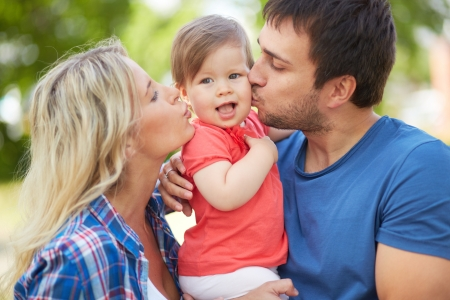childcare: Photo of affectionate parents kissing their small daughter Stock Photo
