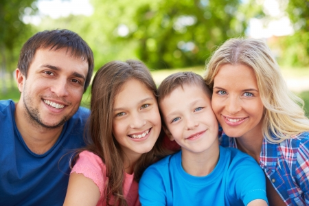 Photo of happy family of four looking at camera outdoors photo