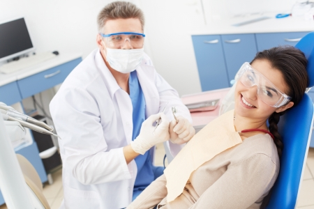 Happy girl in protective eyeglasses looking at camera with toothy smile at the dentist�s photo