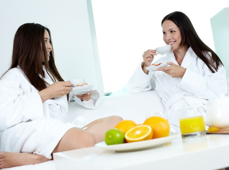 Attractive girls in bathrobes relaxing in spa and drinking tea photo