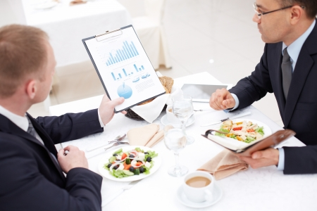 executive meeting: Confident businessmen discussing paper during business lunch