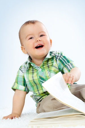 Portrait of happy boy with open book laughing photo
