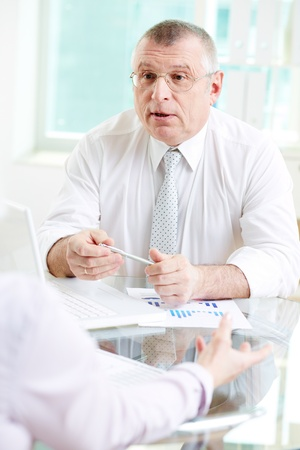 Portrait of mature businessman looking at his partner while talking to her in office photo