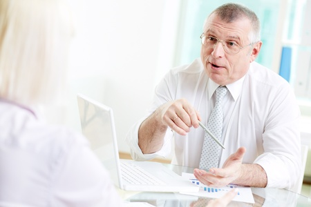 Portrait of mature businessman talking to his partner in office photo