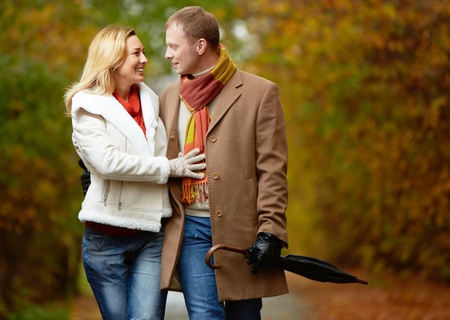 walk in: Portrait of affectionate couple taking a walk in autumnal park Stock Photo