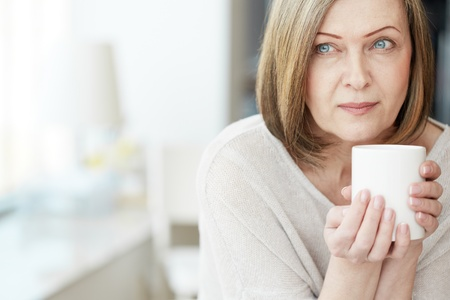 feminine beauty: Portrait of calm mature woman with cup