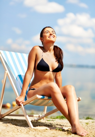 Relaxed young female enjoying rest on the beach on a sunny day photo