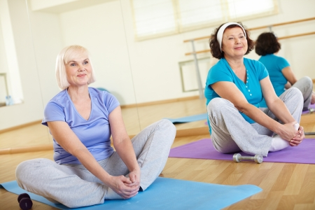 Portrait of two aged women sitting on mats in sport club  photo