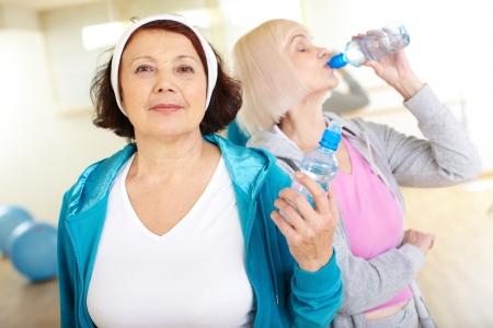 actividad fisica: Retrato de mujer de mediana edad con una botella de plástico mirando a la cámara con su amiga de agua potable en el fondo