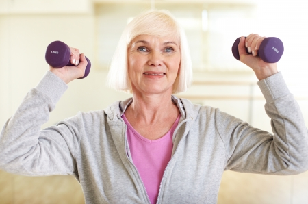 Portrait of aged woman doing exercise with barbells photo