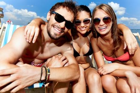 sonnenbaden: Entspannte junge Freunde, die Erholung am Strand Lizenzfreie Bilder