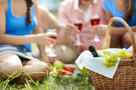 Basket with bottle and grapes on background of cheering friends photo