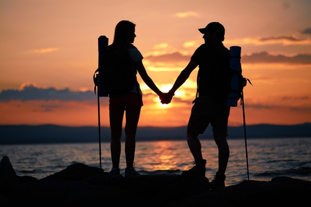 Rear view of couple of hikers holding by hands while standing by water in the evening photo