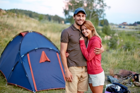resting couple looking at camera in the countryside with tent on background photo