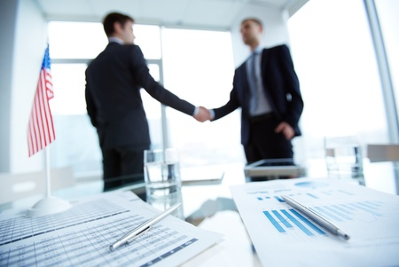 diplomacy: Image of business documents and pens on workplace with two employees handshaking on background