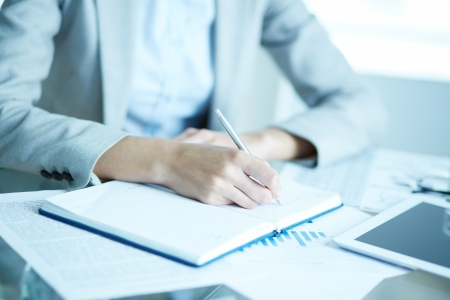 Image of businesswoman writing in notepad at workplace photo