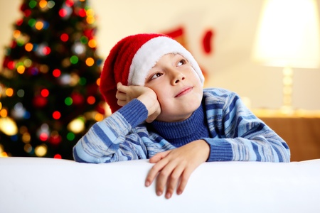 dream home: Image of a cute guy in a Santa hat dreaming of a new year's celebration